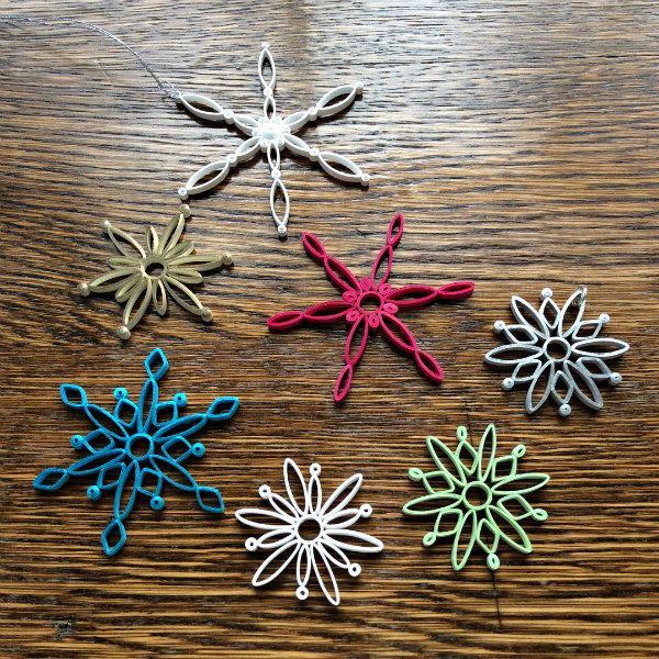 seven quilled snowflakes made with five basic coils