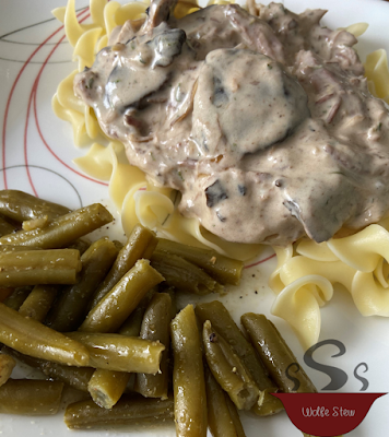 Beef stroganoff on a bed of egg noodles with a side of green beans.