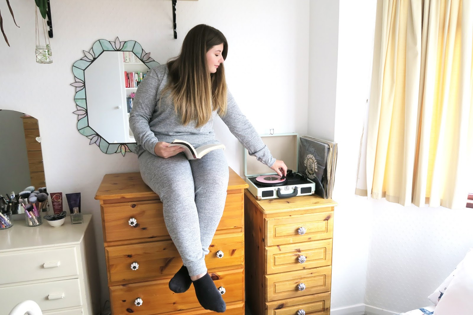 Grace can be seen sitting on top of a set of drawers wearing a grey loungewear set. She is holding a book whilst also leaning over to adjust her record player