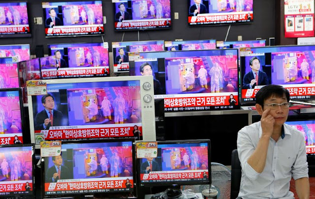 Image Attribute: A sales assistant sits next to TV sets broadcasting a news report on North Korea's fifth nuclear test, in Seoul, South Korea, September 9, 2016.  REUTERS/Kim Hong-Ji