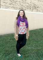 an outfit with a floral blouse, purple scarf, tan cardigan, black jeans, and green flats