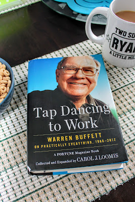 Tap Dancing to Work Warren Buffett on a dining table next to a funny coffee mug.