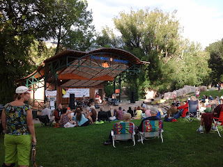 Outdoor music venue along the banks of the Arkansas River with lots of people in lawn chairs, picnics on blankets.