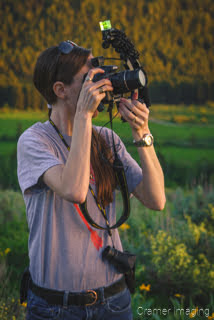 Landscape photographer Audrey holding up a camera and taking a picture by Cramer Imaging