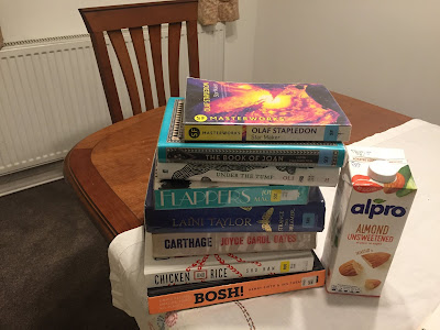 photo of a stack of library books on a wooden table
