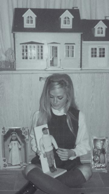 Alejandra Colomera sentada con juguetes de los años 70 en blanco y negro