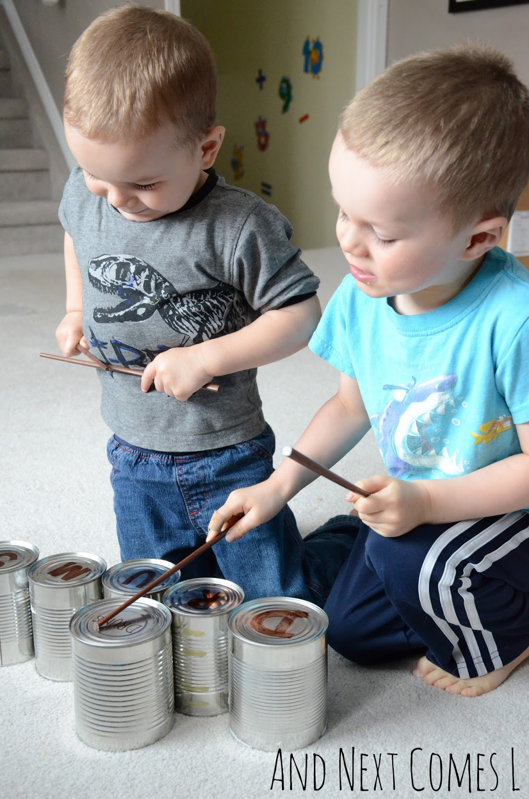 Brothers playing tin can drums together while practicing spelling from And Next Comes L