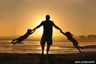 Un papà gioca sulla spiaggia con i suoi due figli