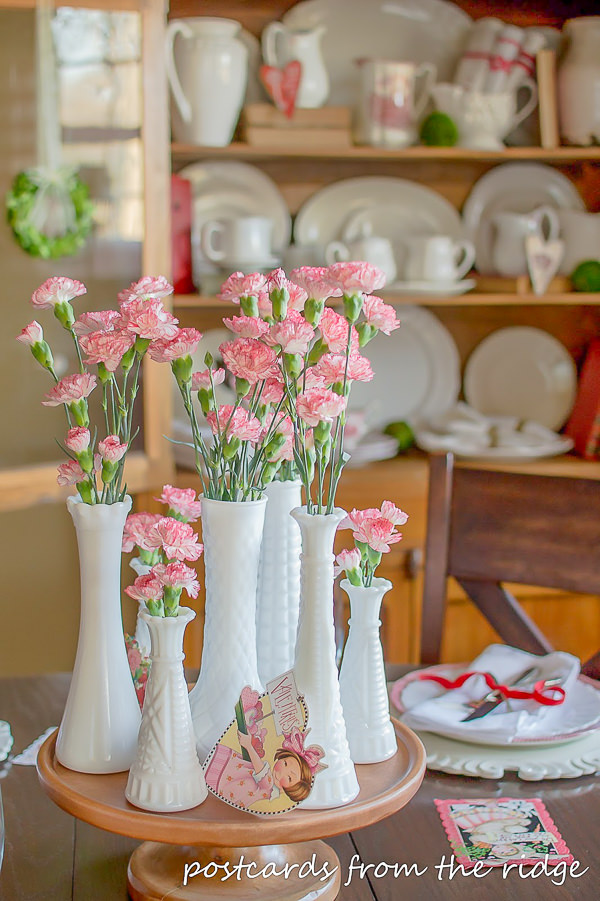 pink carnations in vintage milk glass vases used as a Valentine's day centerpiece