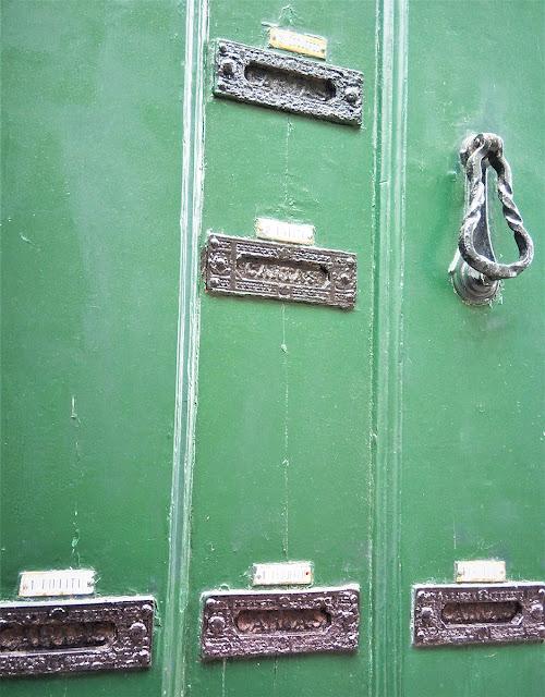 porta antiga com várias caixas de correio