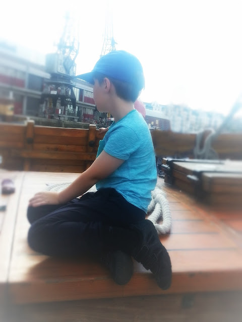 Boy sitting on the deck of The Matthew looking out at the harbour