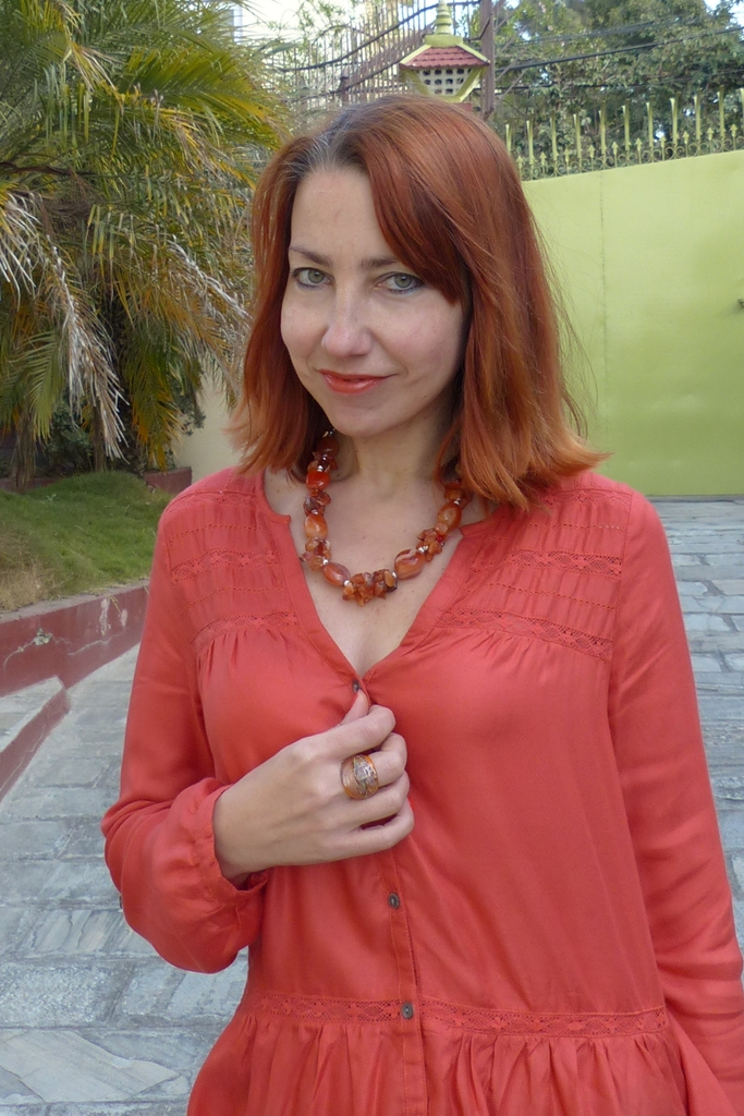 Orange top, cornelian necklace, glass ring