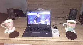 Salontafel met koppen thee, koeken, boxen en laptop met Kensington in beeld