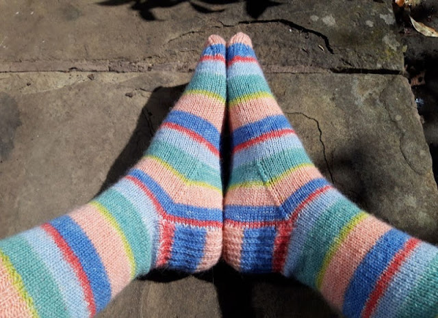 Image shows a pair of multi-coloured striped socks in shades of blue, green and pale pink on a pair of feet, resting on a stone paving flag.