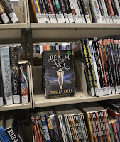 library shelves, sci-fi fantasy section, with the book Realm of Ash by Tasha Sure facing out