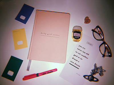 flatlay image of a diary, some paint swatch cards, a pen, a necklace and a pair of glasses on a  white desk
