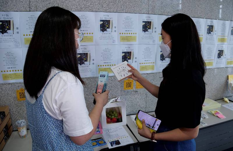 Women take a look at items at a feces currency market at Ulsan National Institute of Science and Technology (photo credit: Reuters)