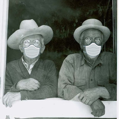 Historic photo of two older men wearing hats and looking out through a barn door. Covid-19 masks have been drawn on their faces.