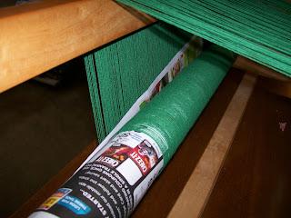 Warp threads wrapped around back warp beam.