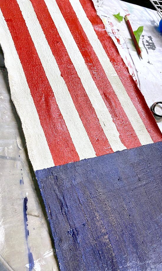 Painted red stripes and blue field on painter's cloth
