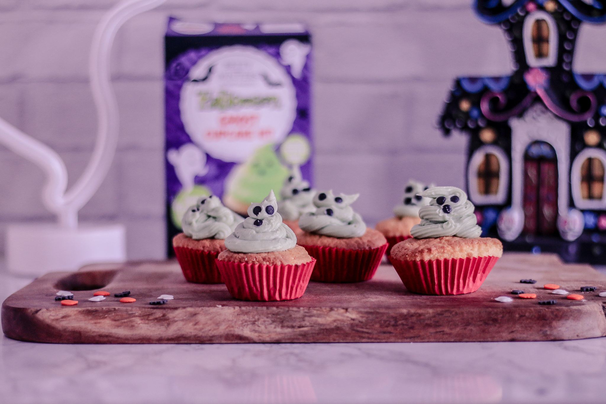 Photo of 6 cupcakes with green icing on a wooden cutting board with the betty winters halloween ghost cupcake box in the background out of focus