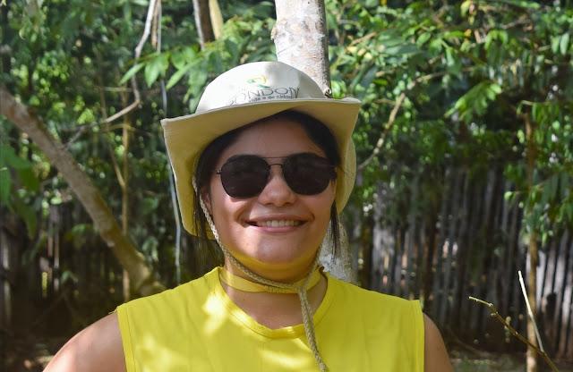 mulher na mata com chapeu e colete  amarelo do projeto rondon