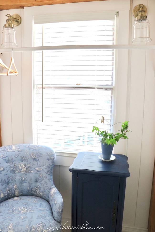 Add French Country style to a room with a blue and white toile print chair and a cabinet painted navy