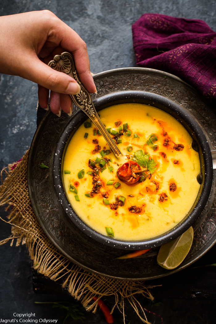 This spring onion gram flour soup is served in a small black saucepan.