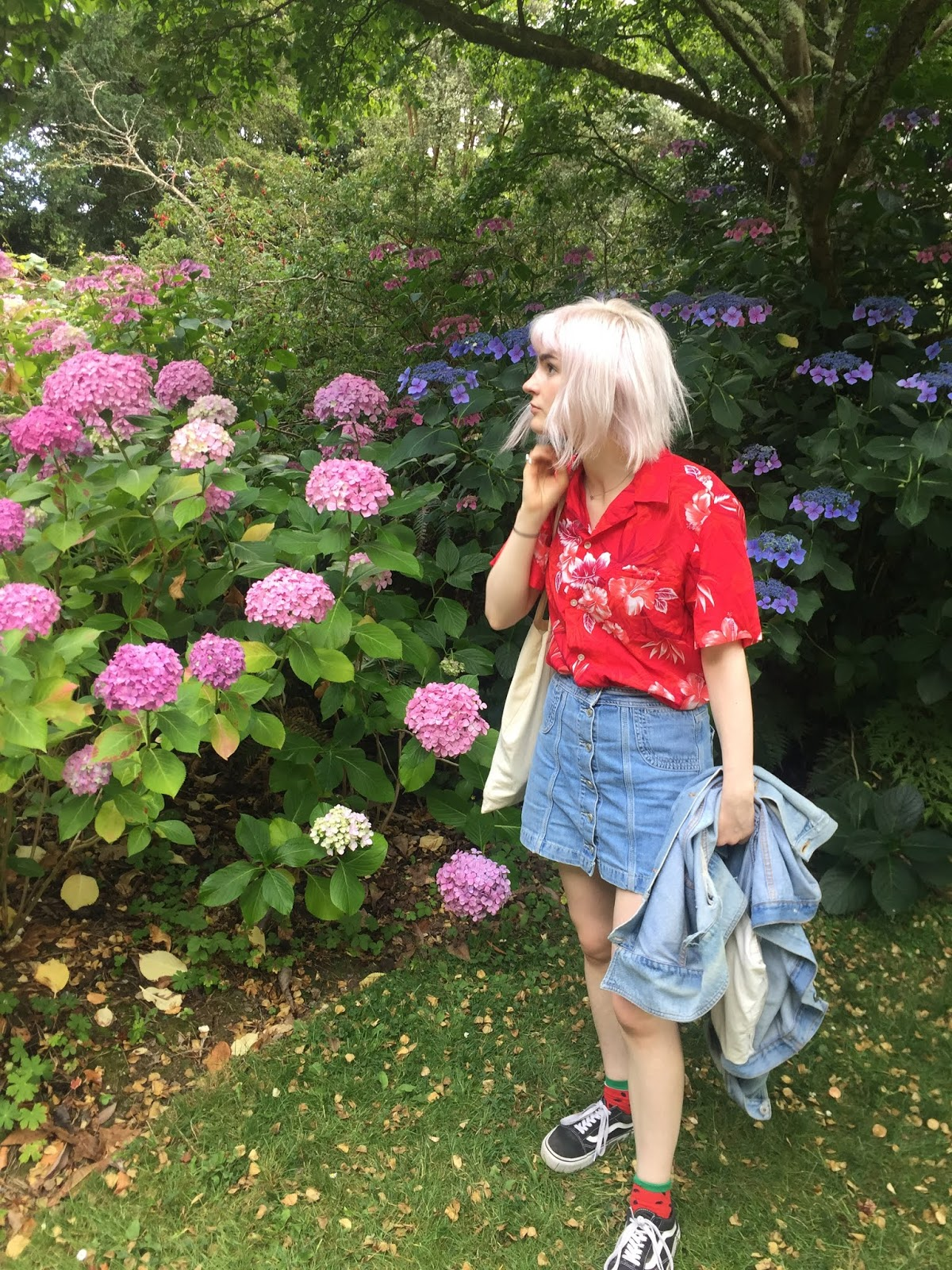 pink haired girl wearing hawaiian shirt and denim skirt standing in front of hydrangeas