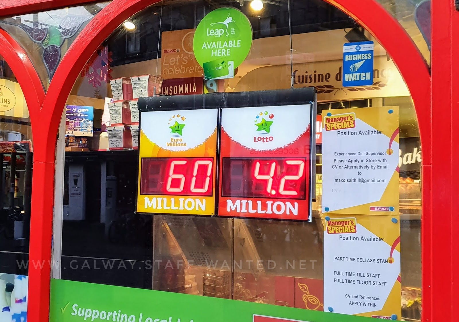 Spar shop window with a Business Watch member sticker, Leap card available here sign, and red LED-based Lotto prize amount signs advising the current prize pool for both Euromillions (60 million) and the Irish Lotto (4.2 milling)