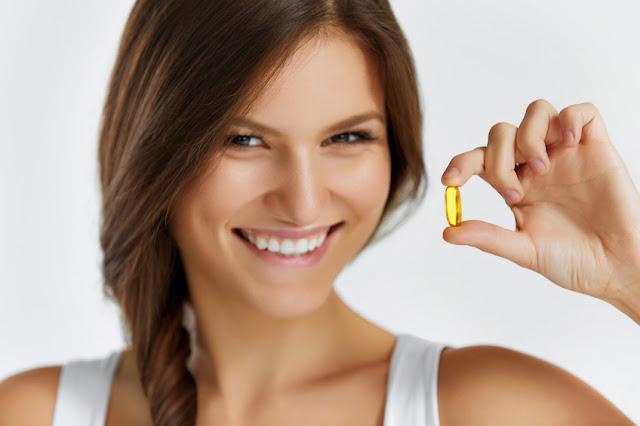 mulher segurando capsula de oleo