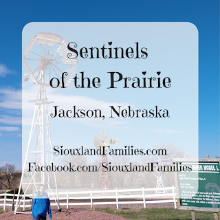 "in the foreground, the words ""Sentinels of the Prairie, Jackson, Nebraska, SiouxlandFamilies.com, Facebook.com/SiouxlandFamilies"", in the background, a boy in a blue sweatshirt stands in front of a white and a yellow antique windmill"