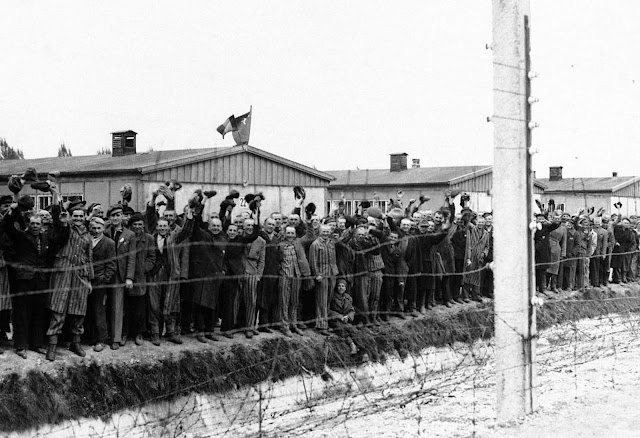 Prisoners at the electric fence of Dachau concentration camp cheer American soldiers in Dachau, Germany in an undated photo. Some of them wear the striped blue and white prison garb. They decorated their huts with flags of all nations which they had made secretly as they heard the guns of the 42nd Rainbow Division getting louder and louder on the approach to Dachau.