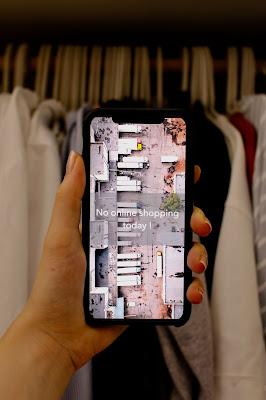 """Móvil delante de un perchero con ropa con el mensaje: """"No online shopping today!"""""""