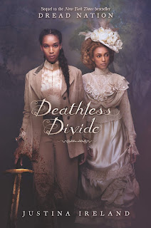 Two Black women in fancy cream and white clothing, the one on the left is holding a sword in her right hand, her sleeve and pant-legs are splattered with blood.