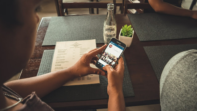 Man using Instagram at a table