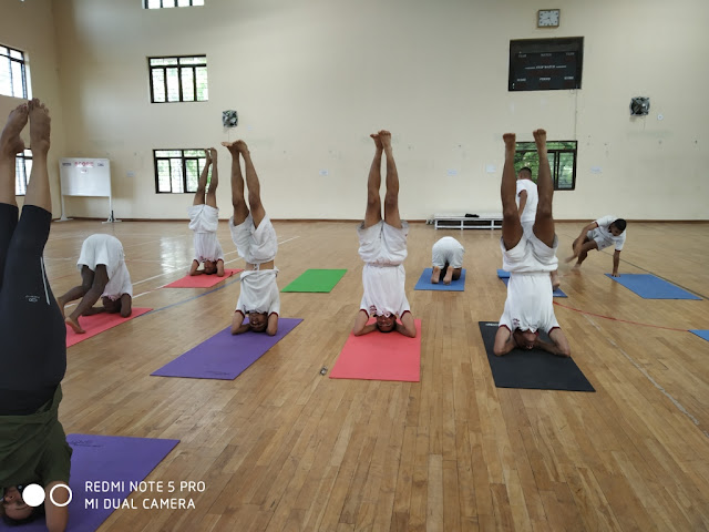 Anita and NDA cadets doing a headstand posture in Yoga