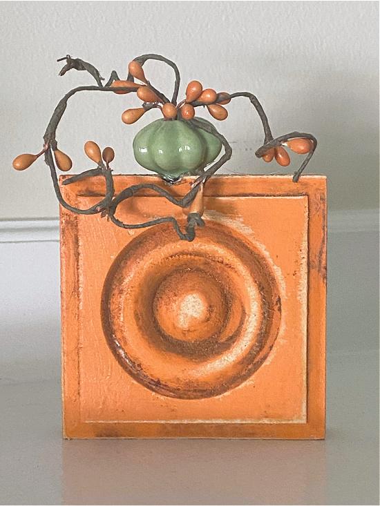 orange wooden block pumpkin with seeded stems
