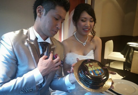 The Japanese newlywed gets a Barcelona-themed cake after their matrimony at the Camp Nou