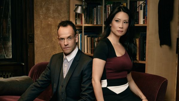 Jonny Lee Miller and Lucy Liu sitting on couch