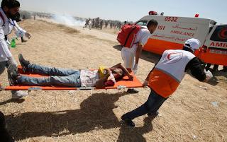 مسعفون فلسطينيون يحملون متظاهرًا جريحًا شرق خان يونس في جنوب قطاع غزة ، خلال مظاهرة