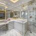 Banheiro com banheira e bancada de maquiagem com porcelanato marmorizado e metais dourados!