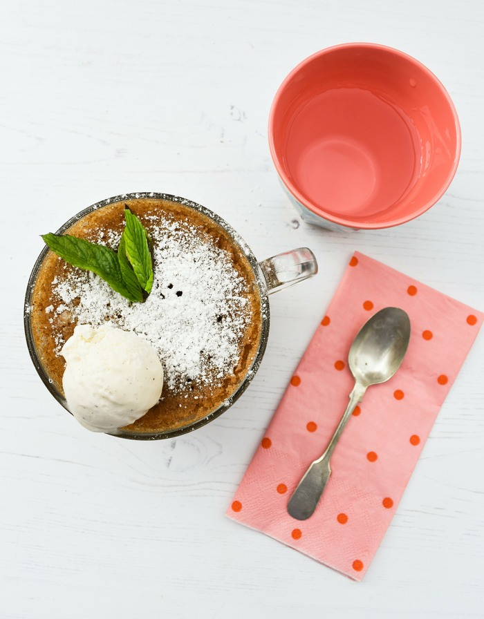 Overhead shot of gingerbread cake in a mug next to pink spotty napkin and a teaspoon
