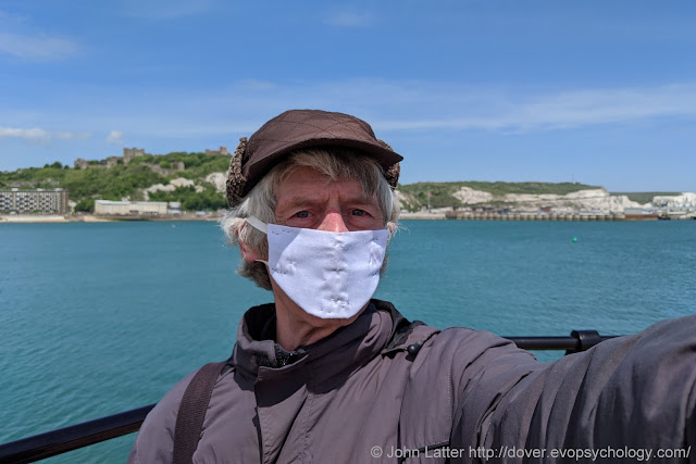 John Latter on the New Marina Pier, Dover Western Docks Revival (DWDR) area of the Port of Dover, Kent, England, wearing a homemade Coronavirus personal protection equipment face mask. Dover Castle's Saxon St Mary-in-Castro church and Roman Pharos on the White Cliffs in background.