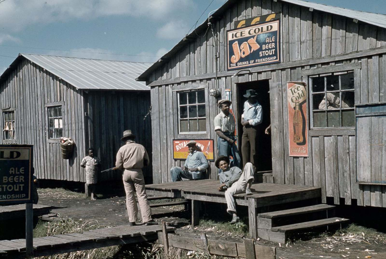 Migrant congregate outside a juke joint during a slack season in Belle Glade, Florida. 1941.