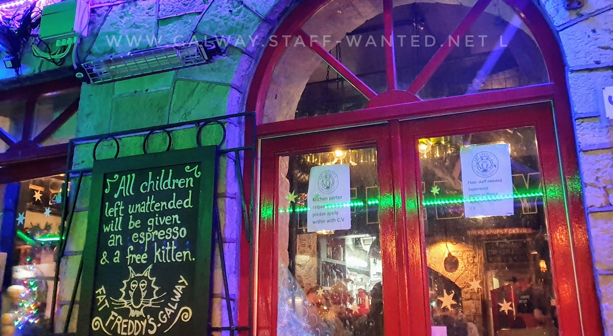 front window of restaurant with star decorations  and a chalk-board with a portrait of freddy the evil restaurant cat, father of the kittens they give away to unsupervised children.