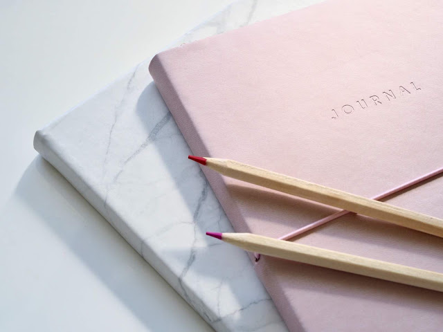 Red and Purple Coloring Pencils on Pink Journal | Photo by Plush Design Studio via Unsplash