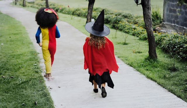 Two children walking away along a path, with one wearing a red cape and a witches hat and one as a clown in a onesie