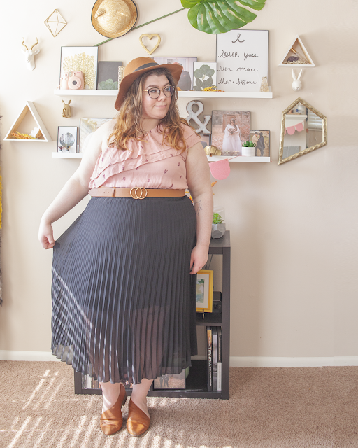 An outfit consisting of a brown panama hat, a pink one shoulder ruffle dress worn as a top tucked into a black pleated midi skirt and brown d'orsay flats.