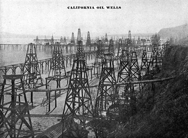 black oil wells on the beach in 1905 California, a photograph